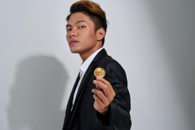 Bitcoin dourado na mão de um homem, símbolo digitall de uma nova moeda virtual