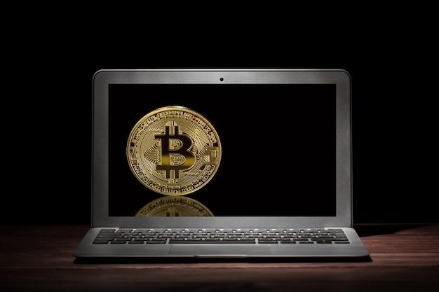 Bitcoin dourado na tela do laptop moderno no quarto escuro na mesa de madeira.