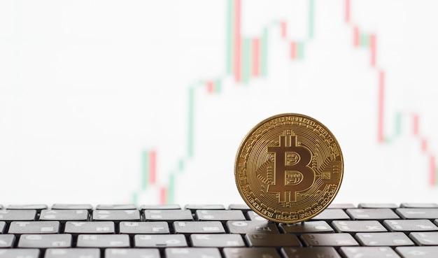 Bitcoin dourado no teclado, no fundo um gráfico branco de crescimento e queda dos preços