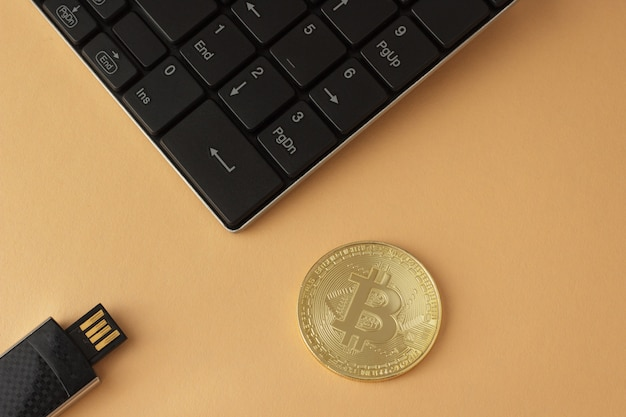Bitcoin dourado, teclado e vista superior da unidade flash