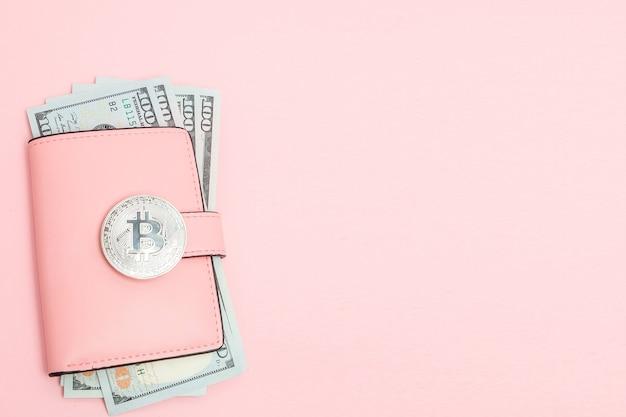 Bitcoin e dólares em uma carteira rosa na rosa.