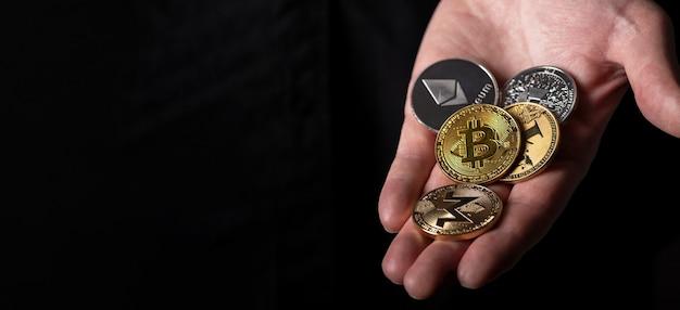 Bitcoin e outras moedas diferentes de criptomoeda na palma da mão masculina sobre fundo preto com espaço de cópia para o texto.