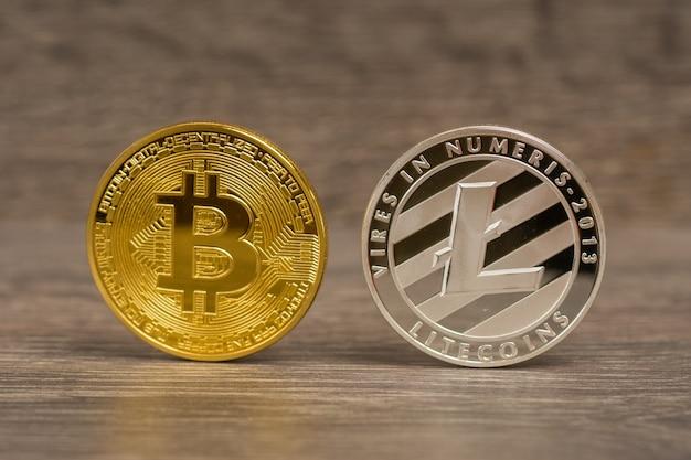 Bitcoin metálico e moedas de litecoin na mesa de madeira