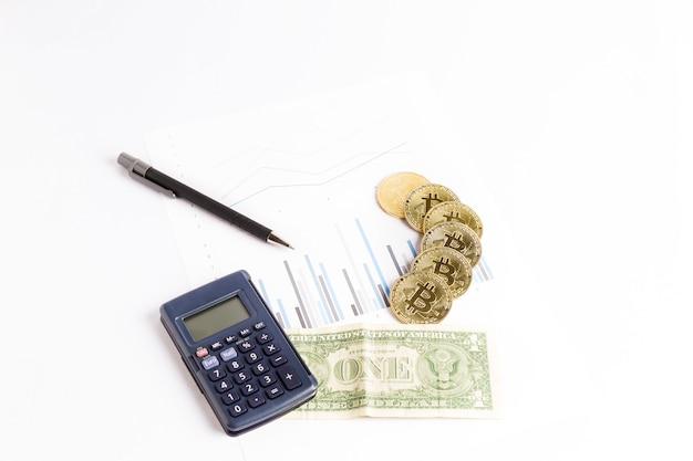 Bitcoin moedas de ouro no gráfico ao lado de uma calculadora, uma caneta e uma nota de dólar