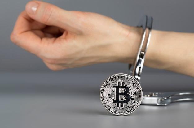 Bitcoin na frente da mão algemado. fechar-se