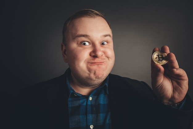 Bitcoin na mão de homem engraçado gordo, símbolo digital de uma nova moeda virtual
