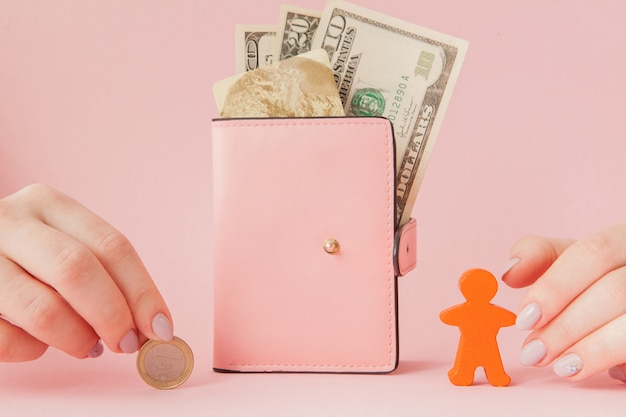 Bitcoin na mão de uma mulher e dólares na carteira rosa com cartão de crédito em um fundo rosa