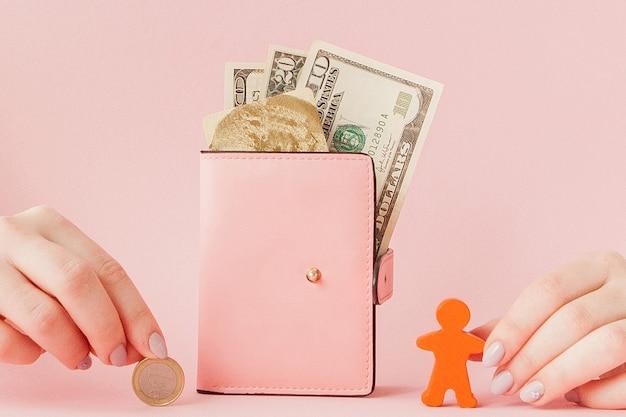 Bitcoin na mão de uma mulher e dólares na carteira rosa com cartão de crédito