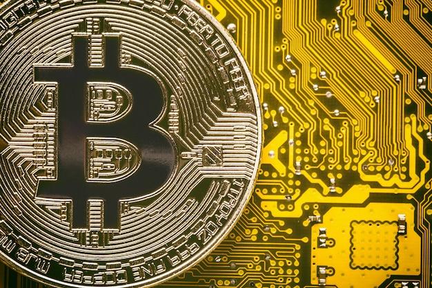 Bitcoin no fim amarelo da placa-mãe do circuito de computador acima.