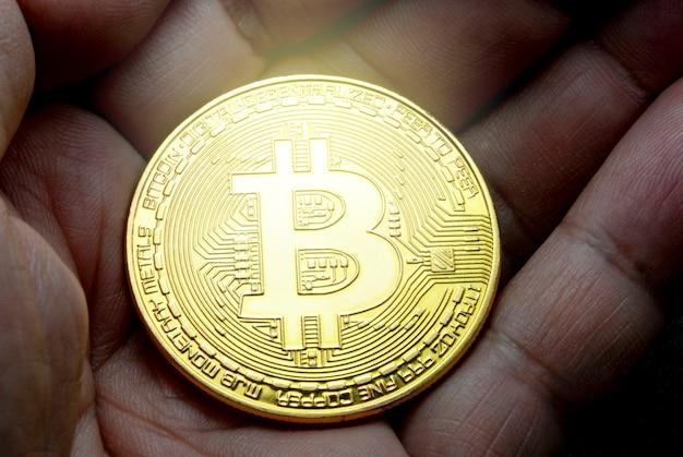 Bitcoin ouro na mão com fundo preto padrão turva
