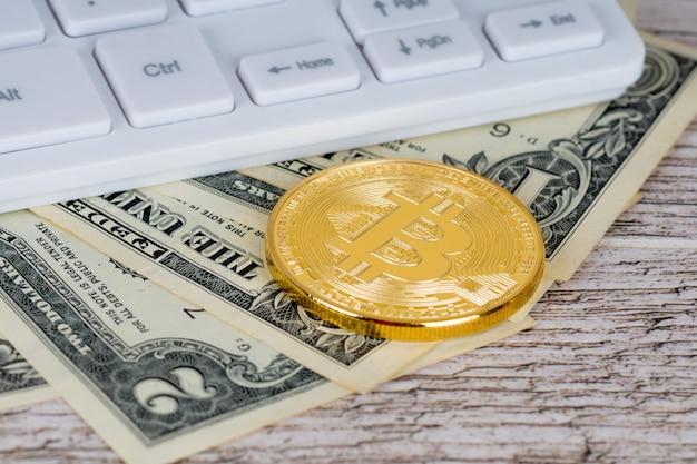 Bitcoin sobre notas de dólar perto do teclado