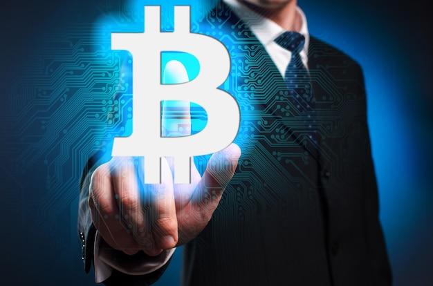 Bitcoin. um homem de terno e gravata clica no dedo indicador na tela virtual.