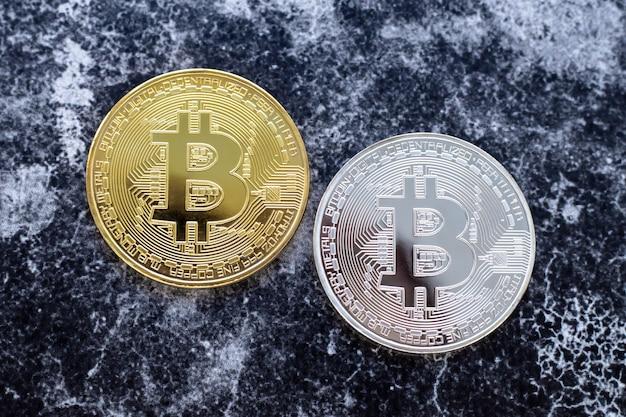 Bitcoins brancos e amarelos em fundo escuro.