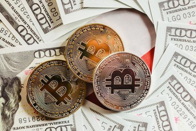 Bitcoins de ouro e prata em notas de cem dólares americanos.