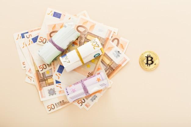 Bitcoins dourados com notas de euro como pano de fundo.