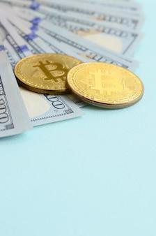 Bitcoins dourados e cem notas de dólar