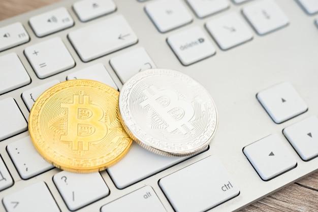 Bitcoins dourados e prateados sobre um teclado branco