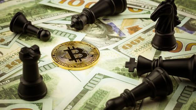 Bitcoins dourados em notas de dólares e uma pilha de perder xadrez