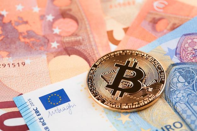 Bitcoins dourados empilhados no fundo das notas de euro.