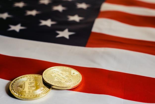 Bitcoins e 100 notas de dólar com fundo da bandeira americana.