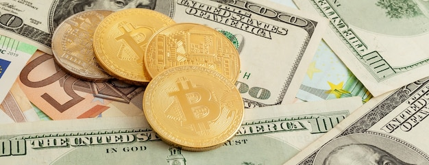 Bitcoins em um fundo de textura do panorama de euros e dólares