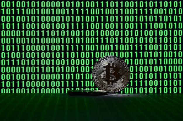 Bitcoins encontra-se em uma superfície de papelão no fundo de um monitor que descreve um código binário
