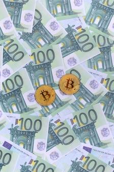 Bitcoins físicos dourados são mentiras em um conjunto de denominações monetárias verdes de 100 euros. um monte de dinheiro forma uma pilha infinita