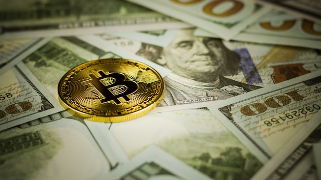 Bitcoins na pilha de um fundo da nota de banco. - conceito de economia e negócios.
