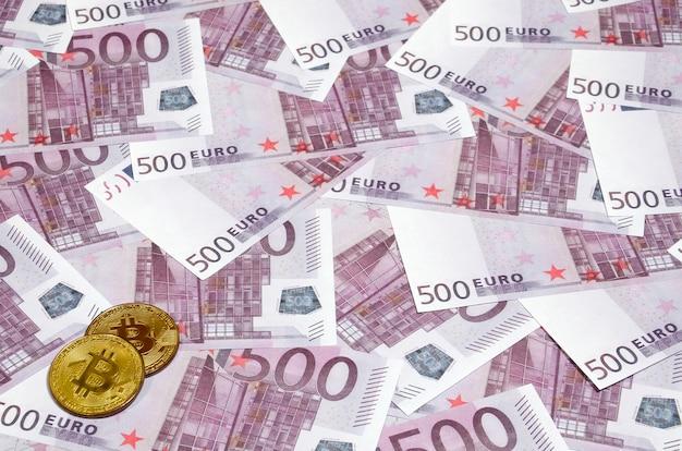 Bitcoins sobre pilha de notas de quinhentos euro