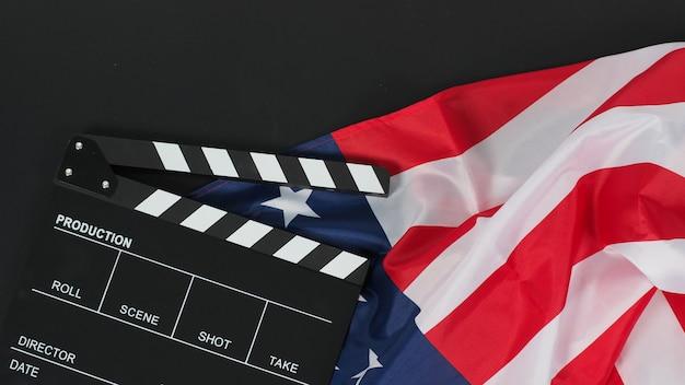 Black clapper board ou movie slate. bandeira dos estados unidos da américa (eua) em fundo preto.