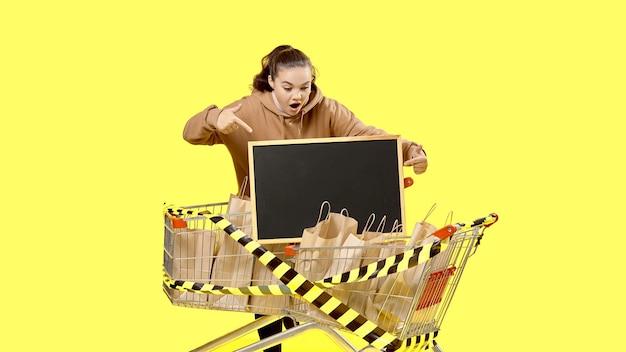 Black friday, a garota aponta em choque para a placa no carrinho de compras