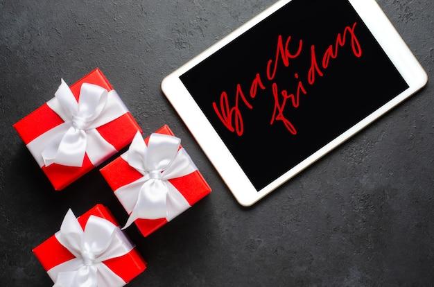 Black friday - escrita a mão vermelha na tela do tablet. caixas de presente com fitas. o conceito de vendas de natal.