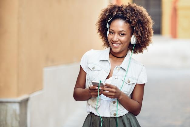 Black girl, afro hairstyle, em rua urbana com fones de ouvido e smartphone