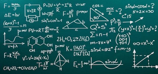 Blackboard inscrito com fórmulas científicas e cálculos em física e matemática.