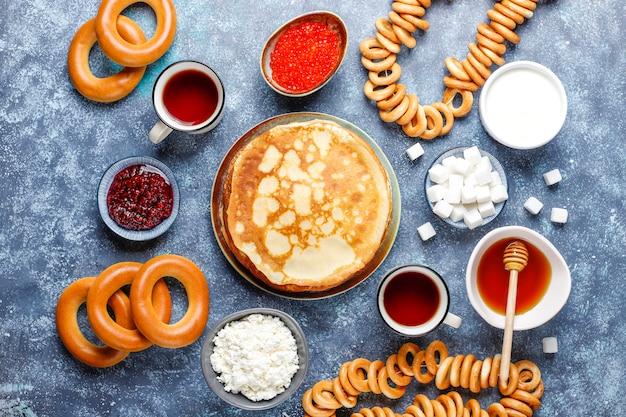 Blini de panqueca russa com geléia de framboesa, mel, creme de leite e caviar vermelho, cubos de açúcar, queijo cottage, bubliks no escuro