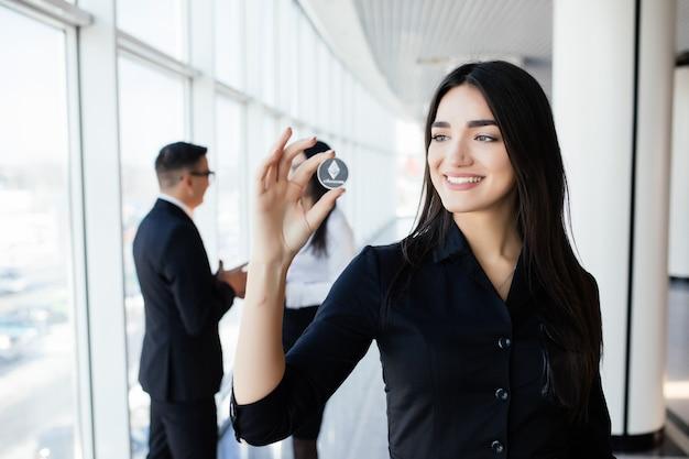 Blockchain e conceito de investimento. líder de mulher de negócios segurando litecoin na frente de sua equipe com as mãos levantadas no escritório.