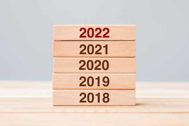 Bloco de 2022 ao longo de 2021, 2020 e 2019, edifício de madeira no fundo da mesa. conceitos de planejamento de negócios, gerenciamento de risco, resolução, estratégia, solução, objetivo, ano novo e feliz feriado