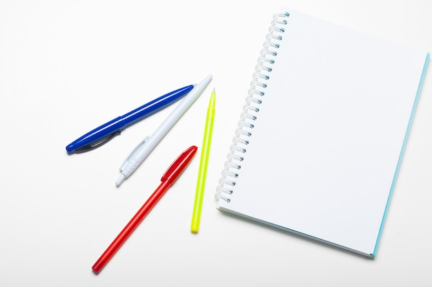 Bloco de anotações caderno e bola pont caneta isolado no branco