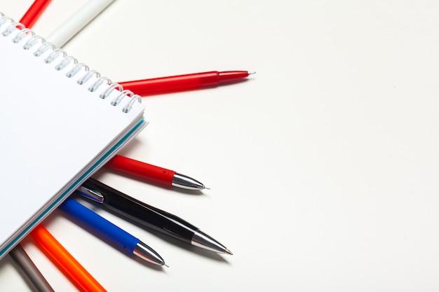 Bloco de anotações caderno e bola pont caneta isolado no fundo branco