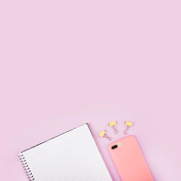 Bloco de anotações; clipes de buldogue e celular na superfície rosa
