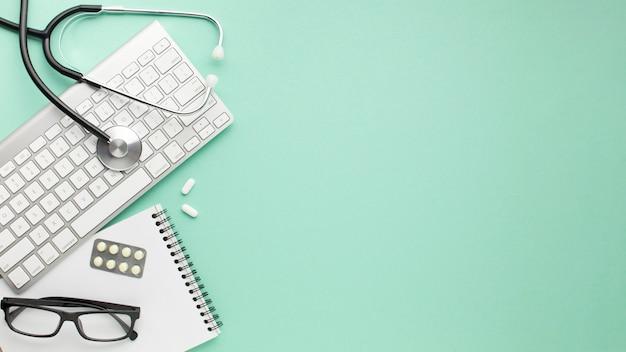 Bloco de anotações; teclado sem fio com estetoscópio e medicamentos sobre a superfície