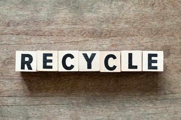 Bloco de carta na palavra reciclar em fundo de madeira