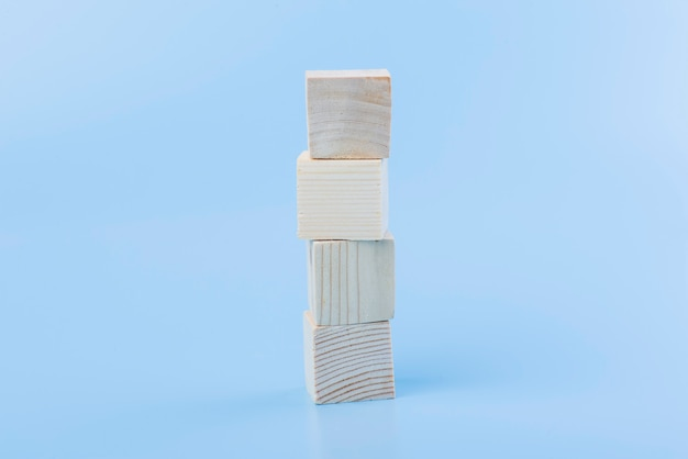 Bloco de cubo de madeira natural em branco sobre fundo azul
