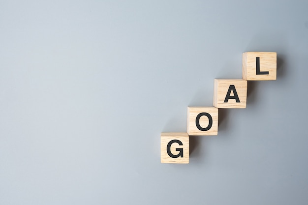 Bloco de cubos de madeira com a palavra do negócio goal. conceito de alvo, objetivo, missão, ação e plano