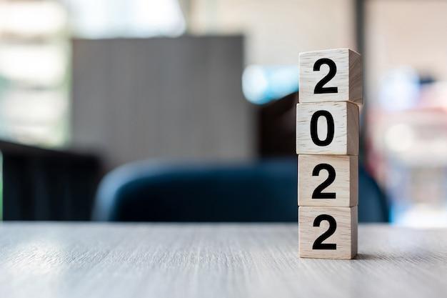 Bloco de cubos de madeira de 2022 no fundo da mesa. resolução, estratégia, solução, objetivo, negócios e conceitos de ano novo e feriados