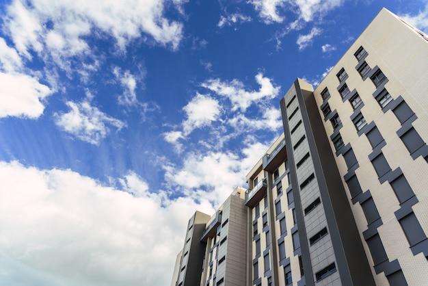Bloco de edifícios residenciais altos com nuvens no fundo