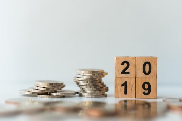Bloco de madeira 2019 com pilha de moedas usando como negócios e conceito financeiro