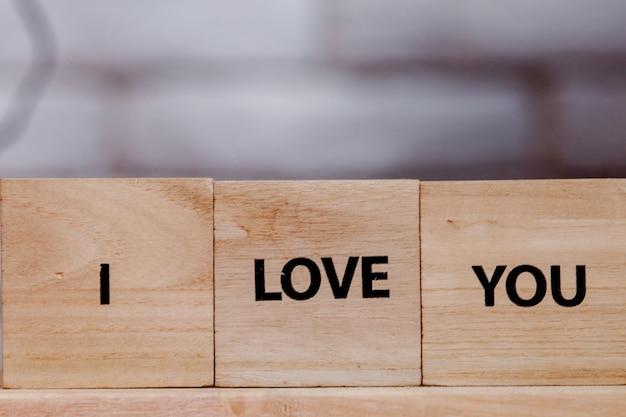 Bloco de madeira com a descrição: i love you on white background, copy space.