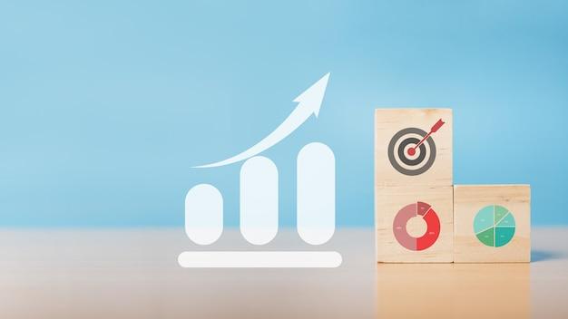 Bloco de madeira com estratégia de negócios de ícone e análise de dados financeiros do gráfico de negociação forex. objetivo e objetivo, conceito de objetivo e objetivo de negócio, desenvolvimento de estratégia da empresa. copie o espaço.