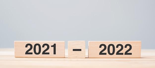 Bloco de madeira de 2021 e 2022 no fundo da mesa. conceitos de resolução, estratégia, contagem regressiva, meta, mudança e feriado de ano novo